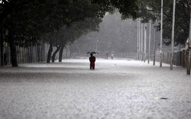 An Indian man shelters under an umbrella